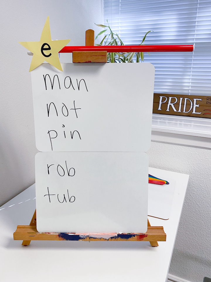 A Magic e wand balanced on top of a white board with the words man, not, pin, rob, and tub written on it.
