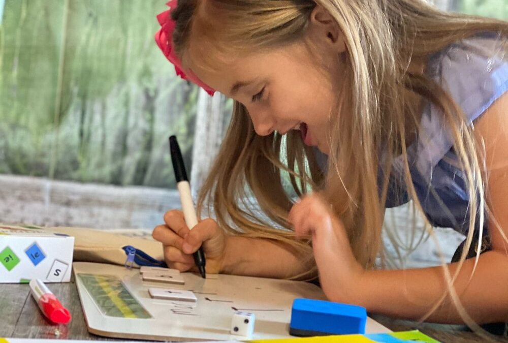 A smiling girl leans over a whiteboard to write with the PRIDE Reading Program Yellow Workbook in the foreground