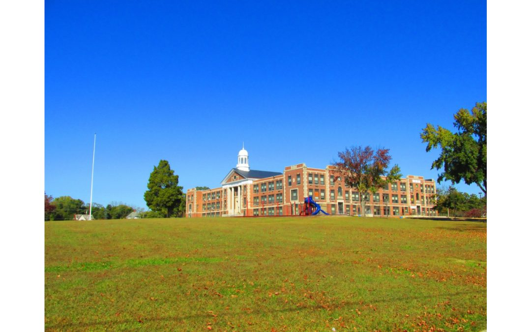 A green meadow in the foreground with a large brick school in the background